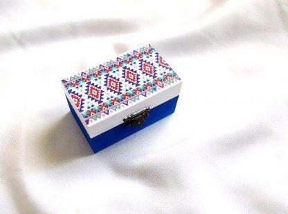 Cutie cu motiv traditional, decorata cu tehnica decupajului, pictata manual, cutie din lemn 33664.Cutie de lemncumotiv traditional,pe un fundal alb pe partea superioara.Fundalul pe partea inferioara a cutiei este de culoare albastra. Culori: alb, albastru, rosu si verde. Cutie decorata cu tehnica decupajului, pictata manual si lacuita cu lac ecologic. Dimensiuni: lungime 9 cm, latime 5,5 cm si inaltime 5 cm.