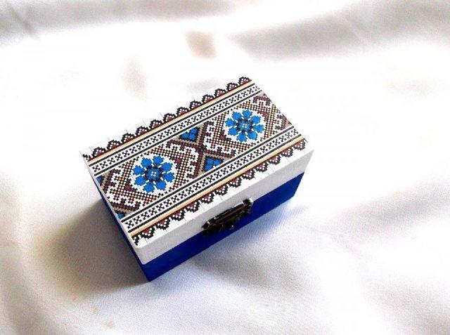 Cutie cu motiv traditional, decorata cu tehnica decupajului, pictata manual, cutie din lemn 33665. Cutie de lemncumotiv traditional,pe un fundal alb pe partea superioara.Fundalul pe partea inferioara a cutiei este de culoare albastra. Culori: alb, albastru, maroniu si galben. Cutie decorata cu tehnica decupajului, pictata manual si lacuita cu lac ecologic. Dimensiuni: lungime 9 cm, latime 5,5 cm si inaltime 5 cm.