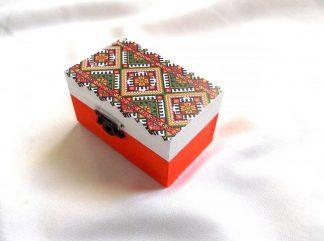 Cutie cu motiv traditional, decorata cu tehnica decupajului, pictata manual, cutie din lemn 33668.Cutie din lemncumotiv traditional,pe un fundal alb pe partea superioara.Fundalul pe partea inferioara a cutiei este de culoare portocalie. Culori: alb, portocaliu, verde, galben si negru. Cutie decorata cu tehnica decupajului, pictata manual si lacuita cu lac ecologic. Dimensiuni: lungime 9 cm, latime 5,5 cm si inaltime 5 cm.