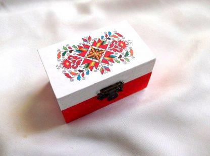 Cutie cu motiv traditional, decorata cu tehnica decupajului, pictata manual, cutie din lemn 33670. Cutie din lemncumotiv traditional,pe un fundal alb pe partea superioara.Fundalul pe partea inferioara a cutiei este de culoare rosu deschis. Culori: diferite culori. Cutiedecorata cu tehnica decupajului,pictata manualsi lacuita cu lac ecologic. Dimensiuni: lungime 9 cm, latime 5,5 cm si inaltime 5 cm.