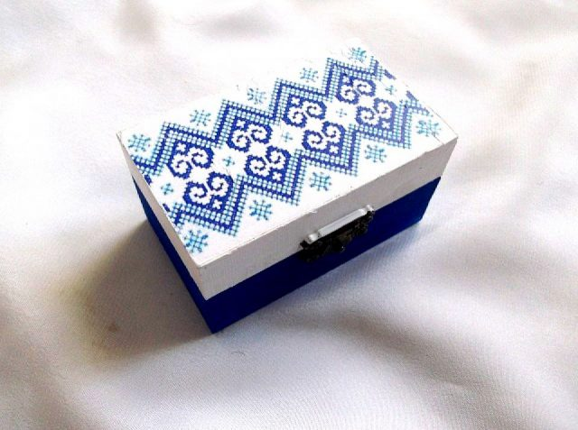 Cutie cu motiv traditional, decorata prin tehnica decupaje, pictata manual, cutie din lemn 33672.Cutie din lemncumotiv traditional,pe un fundal alb pe partea superioara.Fundalul pe partea inferioara a cutiei este de culoare albastru inchis. Culori: alb, albastru si albastru inchis . Cutie decorata cu tehnica decupajului,pictata manualsi lacuita cu lac ecologic. Dimensiuni: lungime 9 cm, latime 5,5 cm si inaltime 5 cm.