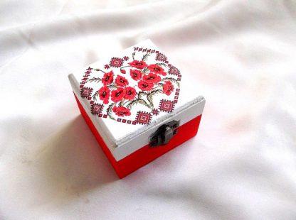 Cutie cu motiv traditional, pictata manual, cutie din lemn 33673.Cutie din lemncumotiv traditional, reprezentand flori de maci,pe un fundal alb pe partea superioara.Fundalul pe partea inferioara a cutiei este de culoare rosu deschis. Culori: alb, rosu deschis, visiniu si negru . Cutia este decorata cu tehnica decupajului,pictata manualsi lacuita cu lac ecologic. Dimensiuni: lungime 8 cm, latime 8 cm si inaltime 6 cm.