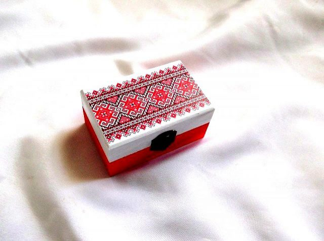 Cutie cu motiv traditional, pictata manual, lacuita cu lac ecologic, cutie din lemn 33663.Cutie de lemncumotiv traditional,pe un fundal alb pe partea superioara.Fundalul pe partea inferioara a cutiei este de culoare rosie. Culori: rosu,negru si alb. Cutie decorata cu tehnica servetelului, pictata manual si lacuita cu lac ecologic. Dimensiuni: lungime 11 cm, latime 7 cm si inaltime 5 cm.