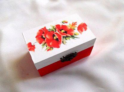 Cutie decorata prin tehnica decupajului, pictata manual, cutie din lemn cu maci33671.Cutie din lemn , cu un fundal alb pe partea superioara, pe care sunt reprezentate flori de maci.Fundalul pe partea inferioara a cutiei este de culoare rosu deschis. Culori: alb, rosu deschis, verde, galben si negru. Cutiedecorata cu tehnica decupajului,pictata manualsi lacuita cu lac ecologic. Dimensiuni: lungime 9 cm, latime 5,5 cm si inaltime 5 cm.