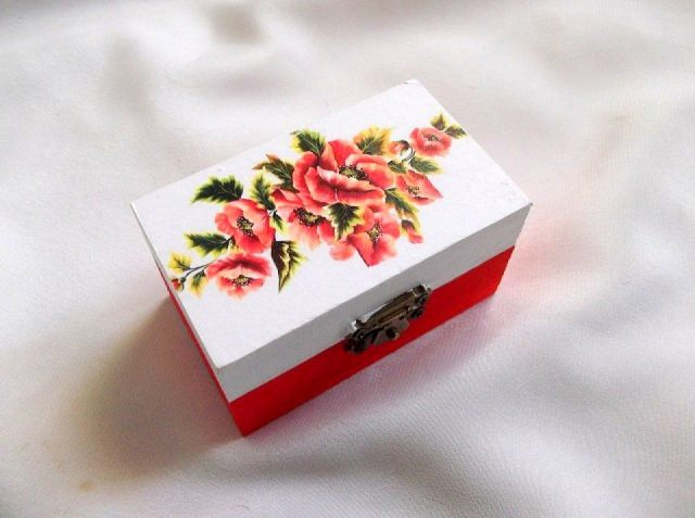 Cutie decorata cu tehnica decupaje, pictata manual, cutie din lemn cu maci 33669.Cutie din lemn ,pe un fundal alb pe partea superioara, pe care sunt reprezentate flori de maci.Fundalul pe partea inferioara a cutiei este de culoare rosu deschis. Culori: alb, rosu deschis, verde si galben. Cutiedecorata cu tehnica decupajului,pictata manualsi lacuita cu lac ecologic. Dimensiuni: lungime 9 cm, latime 5,5 cm si inaltime 5 cm.