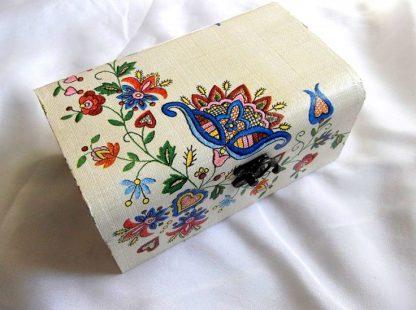 Cutie lemn, design motiv floral 33302.Cutie din lemn, avand ca design un motiv floral, pe un fundal de culoare deschisa, pictata manual si decorata cu tehnica servetelului. Culori : diverse culori. Dimensiuni: lungime 20 cm, latime 13 cm si inaltime 9 cm.