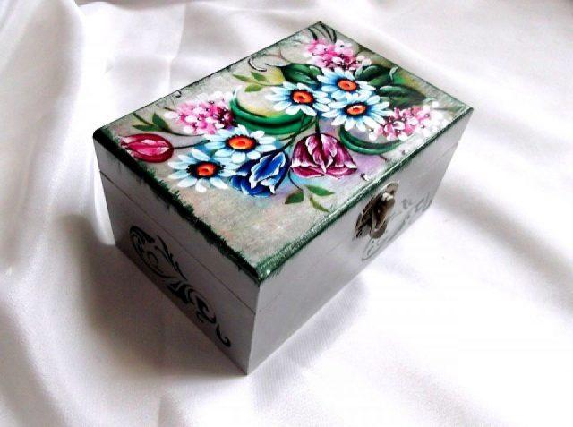 Design cu model floral, cutie din lemn 33705.Produs util femei – cutie pastrare bijuterii si lucruri personale. Design cu model floral / diverse flori printre care lalele si margarete, pe fundal de lemn natur – pe capac. Culori: gri, rosu, verde, albastru, lila si negru.Cutie din lemn, decorata cu tehnica servetelului, pictata manual si lacuita cu lac ecologic. Dimensiuni: lungime 14 cm, latime 10 cm si inaltime 7,5 cm.