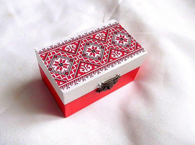 Cutie cu motiv traditional, cutie din lemn 33785.Cutie din lemncumotiv traditional stilizat,pe un fundal alb pe partea superioara.Fundalul pe partea inferioara a cutiei este de culoare rosu deschis. Culori: alb, rosu, rosu deschis si negru. Cutia este decorata cu tehnica decupaje,pictata manualsi lacuita cu lac ecologic. Dimensiuni: lungime 9 cm, latime 5,5 cm si inaltime 5 cm.