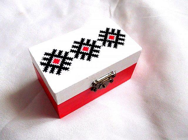 Cutie cu motiv traditional, cutie din lemn 33786.Cutie din lemncumotiv traditional,pe un fundal alb pe partea superioara.Fundalul pe partea inferioara a cutiei este de culoare rosu deschis. Culori: alb, rosu si negru. Cutia este decorata cu tehnica decupaje,pictata manualsi lacuita cu lac ecologic. Dimensiuni: lungime 9 cm, latime 5,5 cm si inaltime 5 cm.
