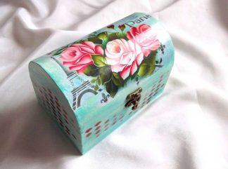 """Design trandafiri rosii, cutie din lemn cu model floral 33796.Cutie din lemn, avand ca design un model floral - trandafiri rosii, pe un fundal de culoare verde-albastra, avand scris cuvantul """"Paris"""" in dreapta sus si o reprezentare a Turnului Eiffel in partea stanga. Cutia este decorata cu hartie decupaje, pictata manual si lacuita cu lac ecologic. Culori : albastru, verde, rosu si galben. Dimensiuni: lungime 17 cm, latime 11 cm si inaltime 12 cm."""