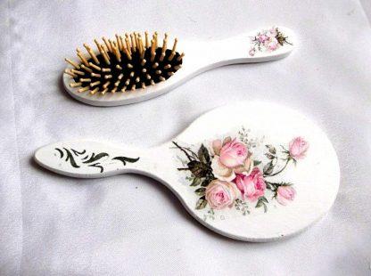 Design trandafiri roz si model ornamental, set oglinda si perie par femei 33864.Produs util femei– set perie par si oglinda cu trandafiri roz, precum si un model ornamental de culoare verde, pe un fundal alb. Culori: alb, roz si verde. Oglinda are o dimensiune mai mare decat peria. Setul este decorat manual cu tehnica servetelului, pictat si lacuit cu lac ecologic. Dimensiuni: inaltime oglinda 25 cm si inaltime perie 21 cm.