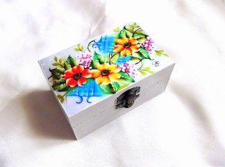 Flori rosii, galbene si roz, cutie din lemn cu model floral 33784.Cutie de lemncu unmodel floral–flori rosii, galbene si roz, pe un fundal gri, usor albastru. Cutia este decorata cu tehnica decupaje, pictata manual si lacuita cu lac ecologic. Culori: gri, albastru, galben, rosu, roz, verde si negru. Dimensiuni: lungime 11 cm, latime 7 cm si inaltime 5 cm.