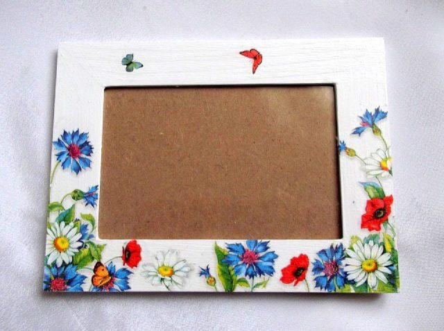 Rama decorata cu margarete, maci si fluturi, rama foto 33846.Produs pentru casa si birou, lucrat manual. Rama pentru fotografii, ce are ca design un model floral – flori de margarete si flori de maci, alaturi de fluturi, pe un fundal alb. Rama este decorata cu tehnica servetelului, pictata cu acrilice si lacuita cu lac ecologic. Culori: alb, galben, rosu, albastru, verde si negru. Rama este potrivita pentru o fotografie de dimensiunile 10 x 15 cm. Dimensiuni rama 20 cm / 15 cm.