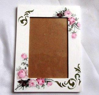 Rama decorata cu trandafiri roz, rama foto 33829.Produs pentru casa si birou, lucrat manual. Rama pentru fotografii, ce are ca design un model floral – trandafiri roz, precum si un model ornamental de culoare neagra, pe un fundal alb spre gri. Rama este decorata cu tehnica servetelului, pictata cu acrilice si lacuita cu lac ecologic. Culori: alb, roz si negru. Rama este potrivita pentru o fotografie de dimensiunile 10 x 15 cm. Dimensiuni rama 20 cm / 15 cm.
