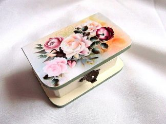 Trandafiri roz si galbeni, cutie din lemn cu model floral 33223.Cutie de lemncu unmodel floral– trandafiri roz si galbeni, pe un fundal albastru deschis si galben, usor rosiatic. Marginile cutiei sunt de culoare verde. Cutia este decorata cu tehnica servetelului si pictata manual. Culori: roz, galben, albastru deschis, verde, verde inchis si rosu. Dimensiuni: lungime 10 cm, latime 6 cm si inaltime 4,5 cm.