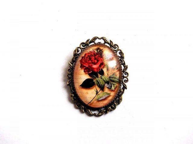 Brosa cu motiv floral, brosa cadou femei 33996. Bijuterie cadou femei, avand ca design un motiv floral - un trandafir rosu, pe un fundal maro. Culori: verde, rosu, maro si negru. Produs din metal si sticla. Dimensiuni: 50 cm / 40 cm.