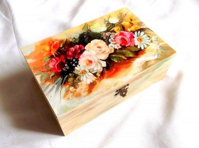 Cutie decorata cu model floral, cutie din lemn 33962.Cutie de lemncu unmodel floral– trandafiri rosii, galbeni si margarete, pe un fundal de culoare galbena si albastra intr-unul din colturi. Partea inferioara a cutiei este de culoare maro deschis, cu tenta de galben sau albastru. Cutia este cu despartitoare, avand 4 camarute pe interior. Culori: alb, maro deschis, galben, rosu, portocaliu, albastru, verde si negru. Dimensiuni: lungime 20 cm, latime 14 cm si inaltime 8 cm.