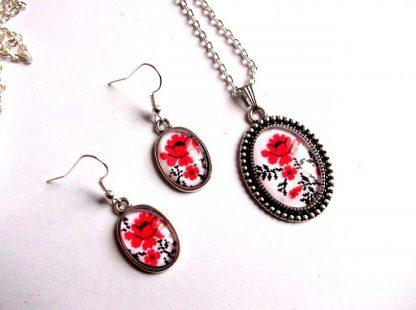 Set bijuterii cu model floral, set pandativ si cercei sticla 33984. Setul este compus dintr-o pereche de cercei cu pandativ, este lucrat pe sticla si reprezinta un motiv floral - trandafiri rosii, pe un fundal alb. Culori: alb, rosu si negru. Dimensiuni pandativ: 32 mm / 25 mm. Un set de bijuterii care poate fi oferit cadou unei domnisoare sau doamne.