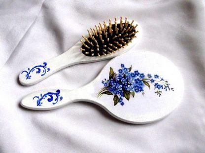 Set model floral si ornamental, set oglinda si perie par femei 33944.Produs util femei– set perie par si oglinda cu model floral – flori albastre, precum si un model ornamental de culoare albastra, pe un fundal alb. Oglinda are o dimensiune mai mare decat peria. Setul este decorat manual cu tehnica servetelului, pictat si lacuit cu lac ecologic. Culori: alb, albastru, verde deschis si verde inchis. Dimensiuni: inaltime oglinda 25 cm si inaltime perie 21 cm.